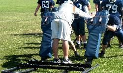 Football coach teaching his players how to use a tackling sled on the field